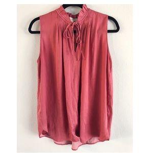 Pink flowy sleeveless blouse.